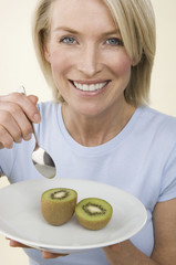 A woman eating a kiwi fruit.