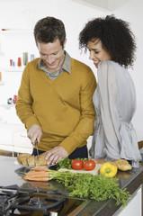 A man and woman, a couple in a kitchen preparing fresh vegetables.