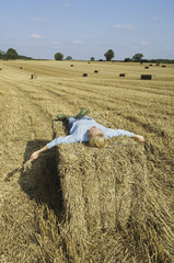 A woman lying on top of a square bale of packed straw at harvest time.