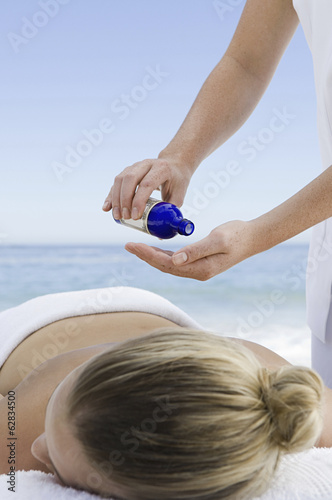 The beach. A young woman having a massage.