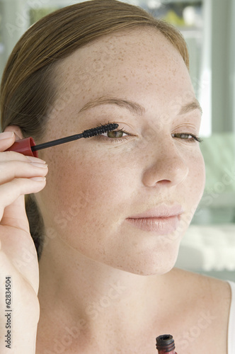 A young woman applying mascara to her eyelashes.