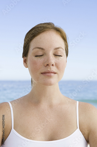 A young woman seated on the beach in a relaxed pose, with her eyes closed.