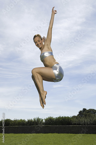 A young woman leaping in the air, knees bent and legs tucked up underneath her. Acrobat.