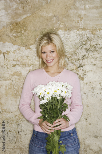 A young woman holding a bunch of daisies.