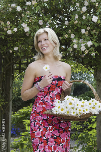 A young woman carrying a basket of cut flowers.