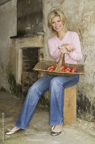 A young woman with a basket of red apples.