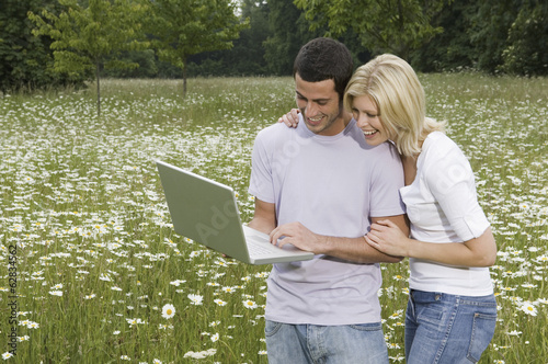 A man and woman in a flower meadow, looking at a laptop screen.