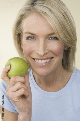 A young woman holding a green apple.