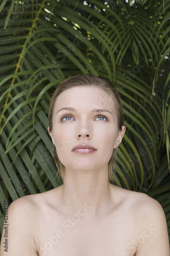 A young woman with bare shoulders, looking upwards. Tropical plants in the background.