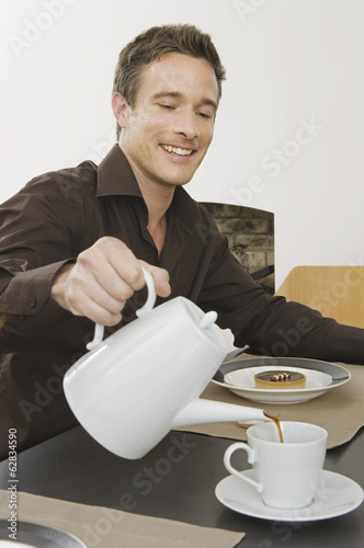 A man sitting pouring a cup of coffee, having breakfast.