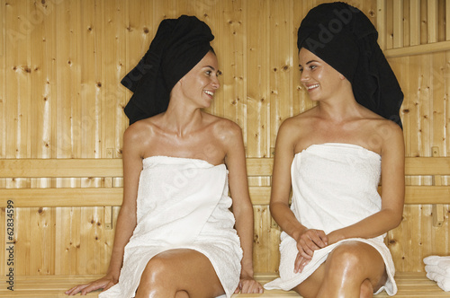 A wooden panelled sauna. Two women seated talking.