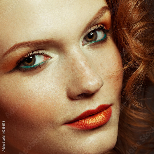 Model with red (ginger) curly hair. Freckles on face. Close up