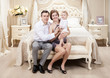 Young happy family with baby in bedroom at home