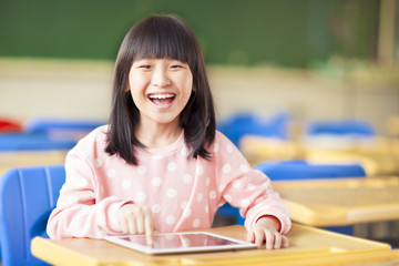 happy little girl using tablet  or ipad