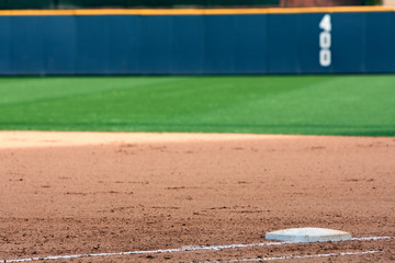 Empty baseball field highlights first base and outfield wall