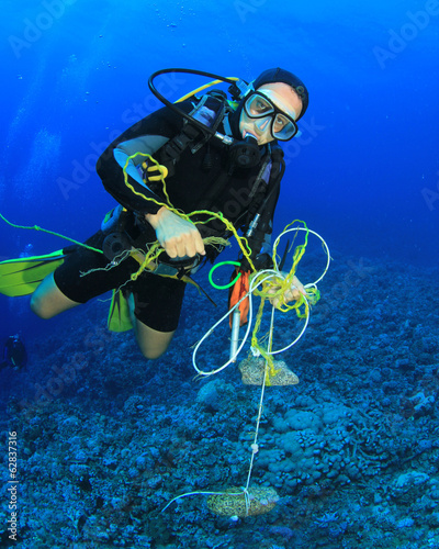 Scuba diver cleans up underwater rubbish - 62837316