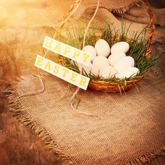 Easter eggs in basket with grass on wooden surface