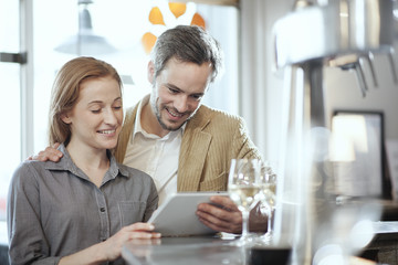 handsome young couple in a bar using a digital tablet