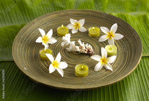 frangipani and candle with shell in bowl on green banana leaf