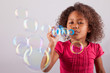 Little African Asian girl blowing soap bubbles
