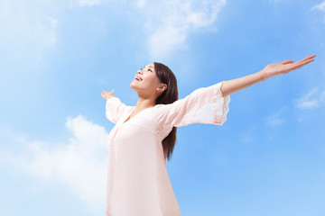 Beautiful woman breathing fresh air with raised arms