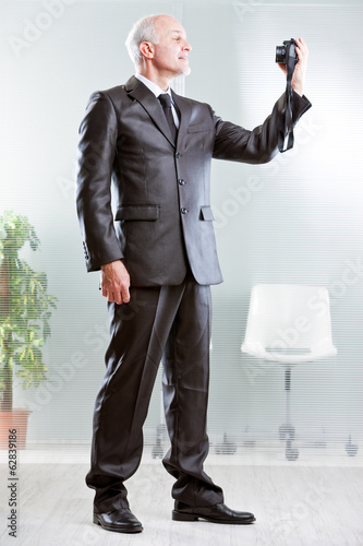 Strong standing businessman making a selfie