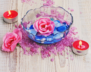 Soap in form of roses in bowl of water on wooden background.