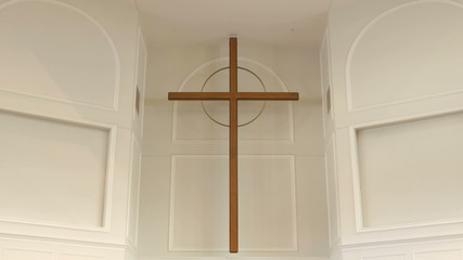 Static shot of a large cross hanging on the wall in a church