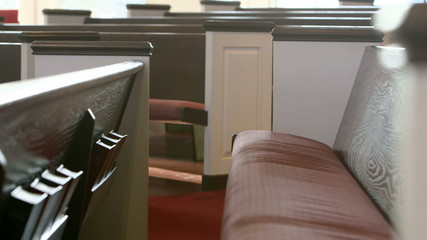 The camera slowly moves past wooden pews in a Christian church