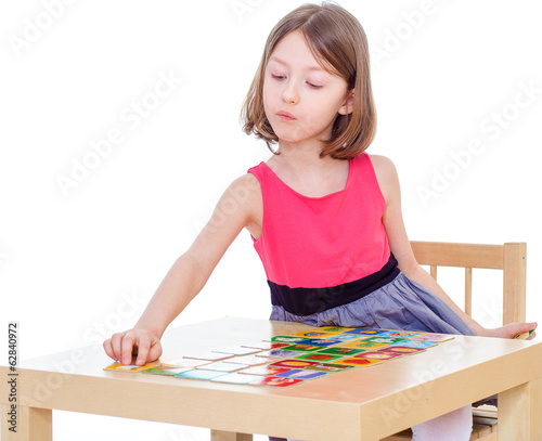 Girl schoolgirl sits at a table and lay cards.