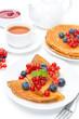 Breakfast with pancakes, fresh berries, jam and black tea