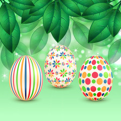 Easter eggs with colorful patterns on a background of spring fol