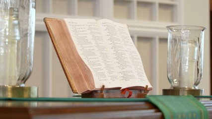 Bible and candles on altar in church
