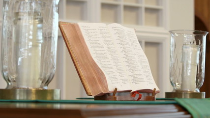 Tracking shot of bible and candles on church altar