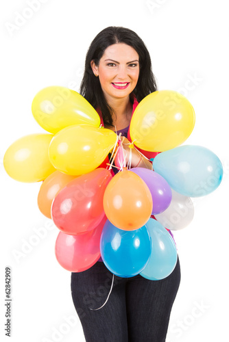 Smiling woman holding plenty balloons