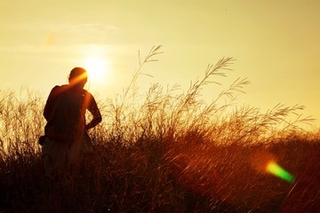trekker walking on grass field when sunset