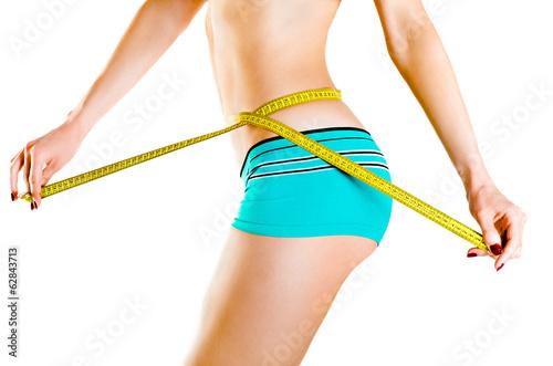 Slim  woman measuring waist - 62843713