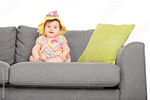 Adorable little baby seated on a couch