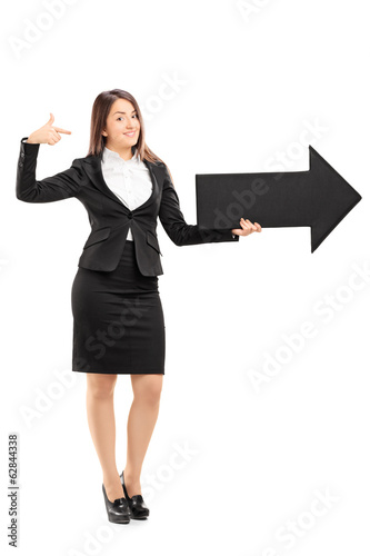 Businesswoman holding a big black arrow