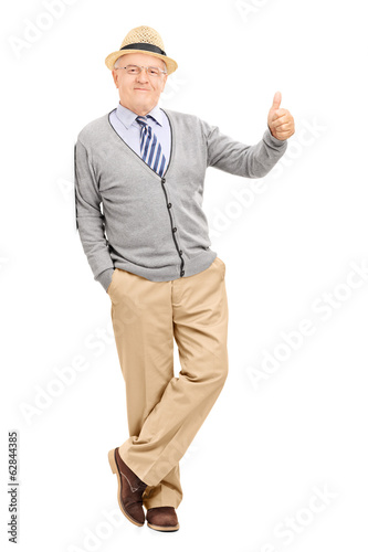Man leaning against a wall and giving thumb up