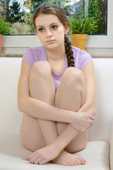 Jugendliche sitzt nachdenklich auf Sofa