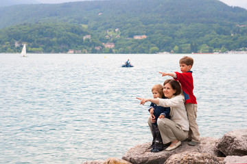 Woman with children on lake brink