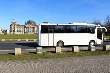 Weisser Reisebus vor Berliner Wahrzeichen Reichstag