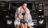 sexy glamour woman with fur coat posing beside a car