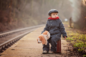 Boy, sitting on a suitcase, waiting for a train