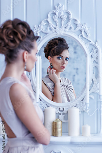 Fashion portrait of young beautiful woman looking in antique mir