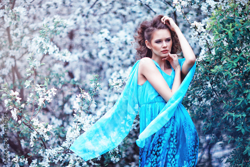 Beautiful woman in blue dress among blossom apple trees, fashion