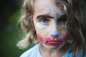 A young girl with a face decorated with face paints, wearing an unamused expression.