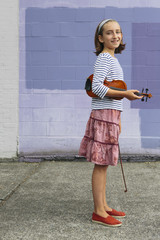 A ten year old girl holding a violin under her arm and a bow in her hand.