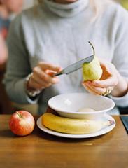A woman slicing a fresh pear. Apple and banana.
